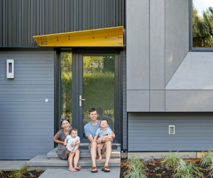 Family sitting in front of a passive house